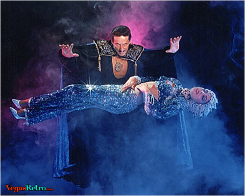 Photo of magician Barclay Shaw levitating a showgirl