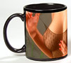 Photo of nearly bare breasts on a black coffee mug